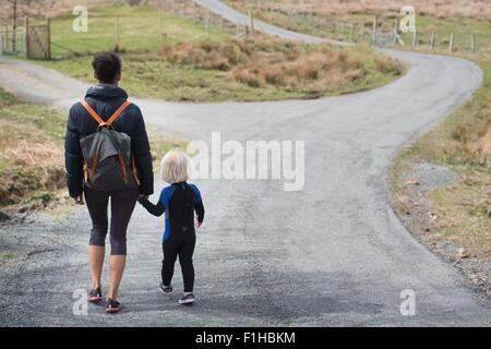 Mother and son walking on country road holding hands, rear view - Stock Photo