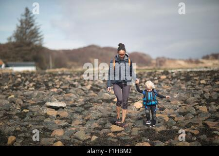 Mother and son holding hands walking on rocks - Stock Photo