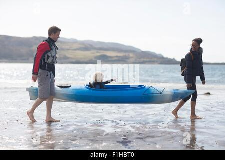 Parents carrying son in canoe on beach, Loch Eishort, Isle of Skye, Hebrides, Scotland - Stock Photo