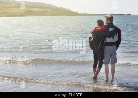 Mid adult couple with arms around each other on beach, Loch Eishort, Isle of Skye, Hebrides, Scotland - Stock Photo