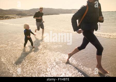 Family running on beach, Loch Eishort, Isle of Skye, Hebrides, Scotland - Stock Photo