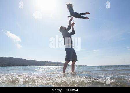 Father throwing son in air on beach, Loch Eishort, Isle of Skye, Hebrides, Scotland - Stock Photo