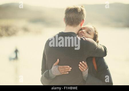 Mid adult couple hugging in sunlight - Stock Photo