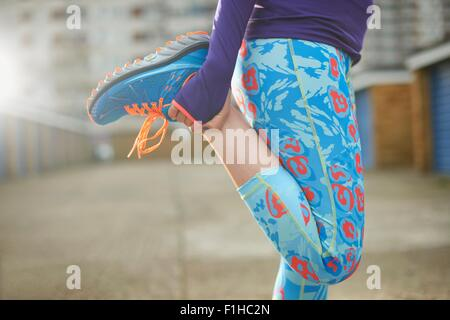 Cropped view of woman bending leg and stretching before exercise - Stock Photo
