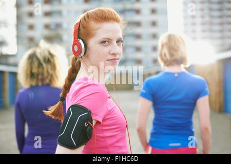 Portrait of woman wearing armband and headphones before exercise looking over shoulder at camera - Stock Photo