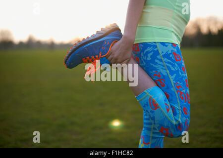 Cropped image of woman stretching leg for exercise in park - Stock Photo