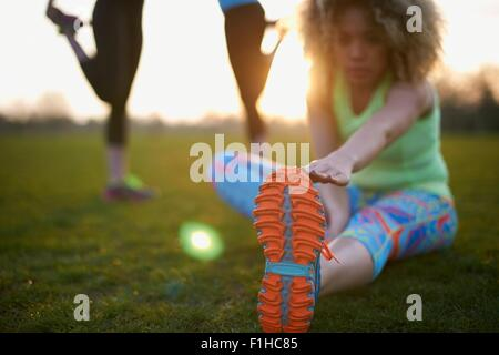 Portrait of woman stretching before exercise in park - Stock Photo