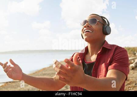 Young man on beach wearing headphones and sunglasses, arms raised - Stock Photo