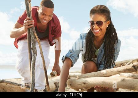 Young couple on beach gathering driftwood together - Stock Photo