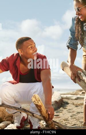 Young couple on beach gathering driftwood together, face to face - Stock Photo