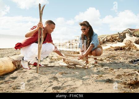 Young couple crouching on beach building campfire with drftwood - Stock Photo