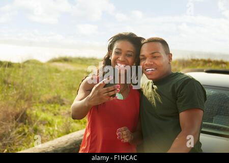 Young couple using smartphone, taking selfie - Stock Photo