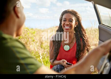 Young woman at open car door holding smartphone smiling