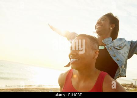 Young woman with arms raised standing behind young man - Stock Photo