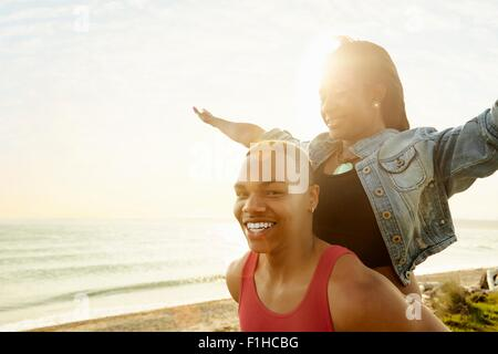 Young woman with arms raised standing behind young man, looking at camera - Stock Photo