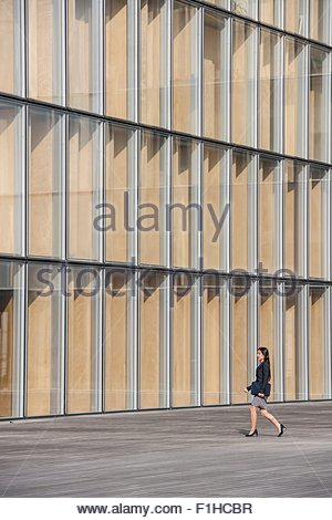 Businesswoman walking past glass facade, Paris, Île-de-France, France - Stock Photo