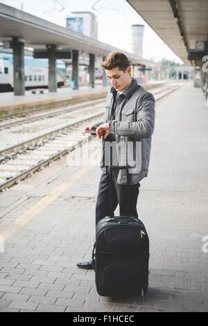 Portrait of young businessman commuter checking wristwatch for the time at train station. - Stock Photo