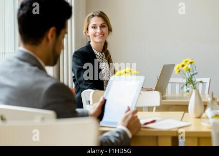 Young man and woman in cafe using laptop and digital tablet - Stock Photo
