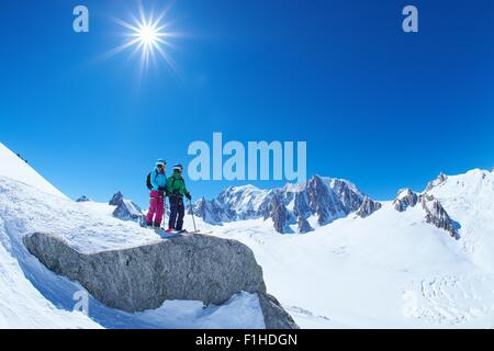 Male and female skiers looking out from ridge on Mont Blanc massif, Graian Alps, France - Stock Photo