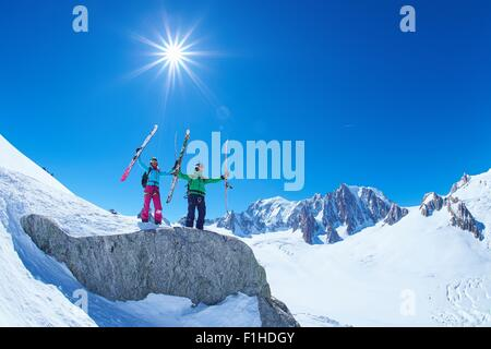 Male and female skiers holding up ski's on Mont Blanc massif, Graian Alps, France - Stock Photo