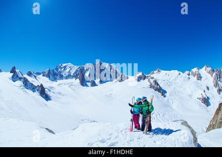 Mature male and female skiers on ridge at Mont Blanc massif, Graian Alps, France - Stock Photo