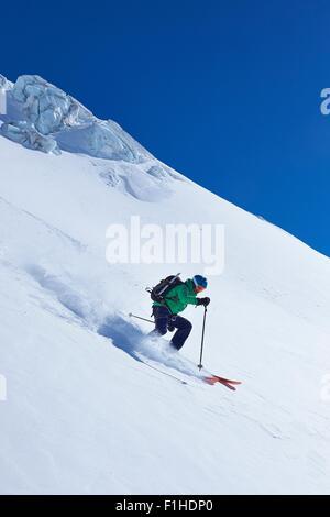 Mature male skier speeding down Mont Blanc massif, Graian Alps, France - Stock Photo