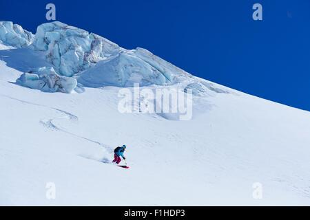 Female skier moving down Mont Blanc massif, Graian Alps, France - Stock Photo