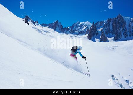 Mature female skier moving down Mont Blanc massif, Graian Alps, France - Stock Photo