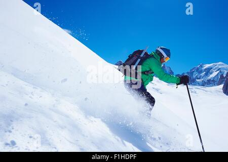 Mature male skier speeding downhill on Mont Blanc massif, Graian Alps, France - Stock Photo