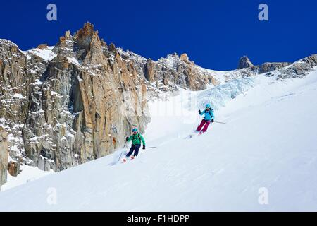 Male and female skiers skiing down Mont Blanc massif, Graian Alps, France - Stock Photo