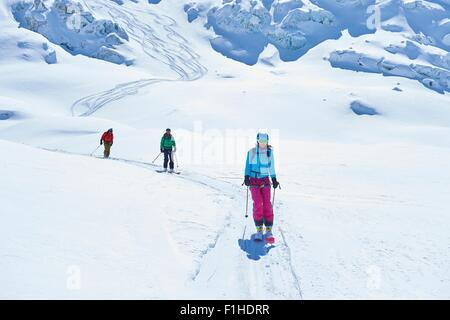 Row of three adult skiers skiing down Mont Blanc massif, Graian Alps, France - Stock Photo