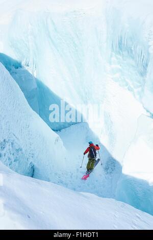 Male skier skiing down ravine on Mont Blanc massif, Graian Alps, France - Stock Photo