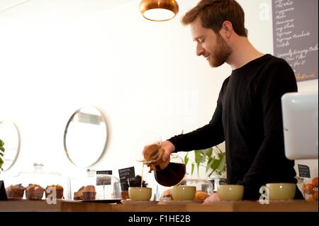Cafe waiter pouring fresh filter coffee into cups - Stock Photo