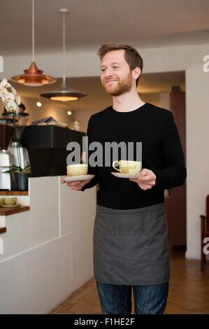Cafe waiter serving cups of fresh coffee - Stock Photo