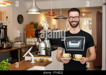 Portrait of cafe waiter serving cups of coffee - Stock Photo