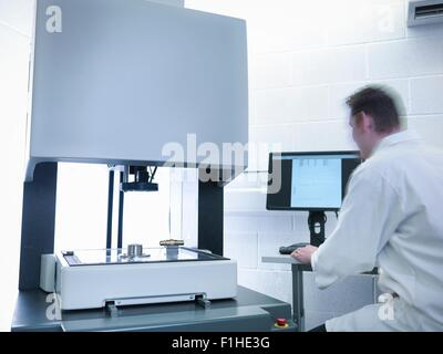 Engineer measuring parts in quality control room - Stock Photo
