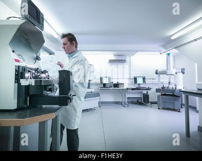 Quality control engineer measuring parts in quality control room - Stock Photo