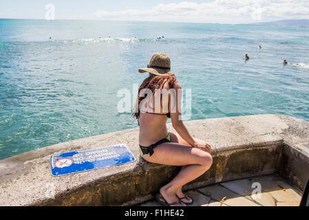 Young woman wearing bikini looking down on Waikiki Beach, Hawaii, USA - Stock Photo