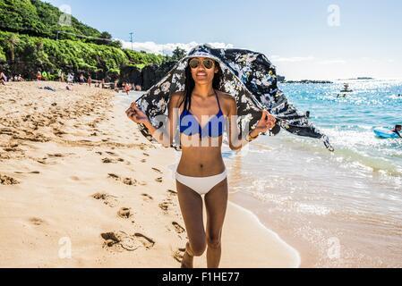 Young woman wearing bikini holding scarf over her head on  Waimea Beach, Oahu, Hawaii, USA - Stock Photo