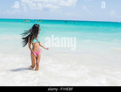 Young woman wearing bikini paddling in sea on Kailua beach, Oahu, Hawaii, USA - Stock Photo