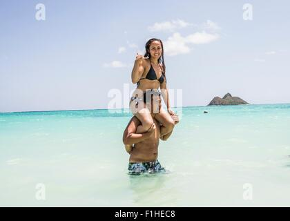 Portrait of young woman getting shoulder ride from boyfriend in sea at Lanikai Beach, Oahu, Hawaii, USA - Stock Photo