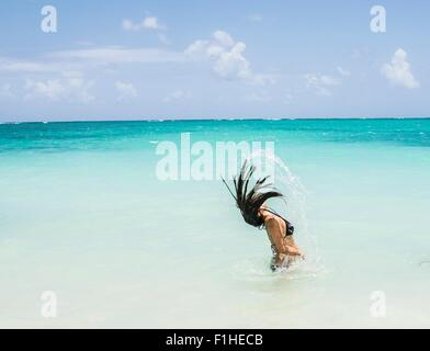 Side view of young woman throwing long wet hair back in sea at Lanikai Beach, Oahu, Hawaii, USA - Stock Photo