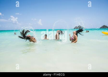 Side view of young women throwing long wet hair back in sea at Lanikai Beach, Oahu, Hawaii, USA - Stock Photo