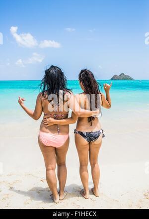 Rear view of two young women wearing bikinis on Lanikai Beach, Oahu, Hawaii, USA - Stock Photo