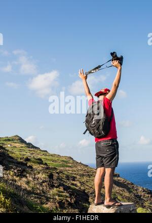 Young male tourist holding up his digital SLR on Makapuu coast path, Oahu, Hawaii, USA - Stock Photo