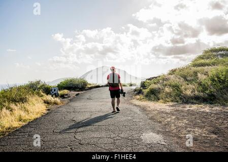 Young male tourist strolling with digital SLR on Makapuu coast path, Oahu, Hawaii, USA - Stock Photo