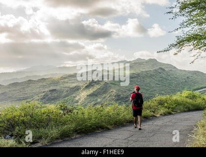 Young male tourist photographing with digital SLR on Makapuu coast path, Oahu, Hawaii, USA - Stock Photo