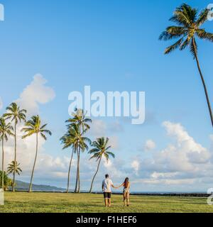 Rear view of young couple strolling near Kaaawa beach, Oahu, Hawaii, USA - Stock Photo