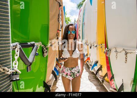 Portrait of young woman standing between surfboards wearing bikini , Waikiki beach, Oahu, Hawaii, USA - Stock Photo