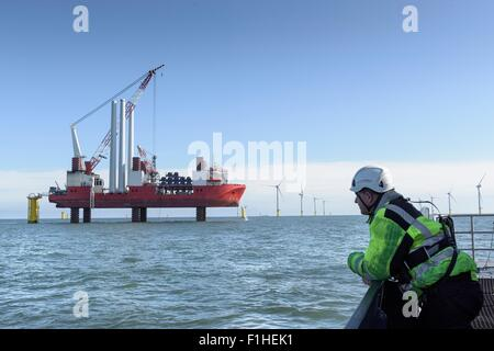 Worker looking at construction ship and offshore windfarm - Stock Photo